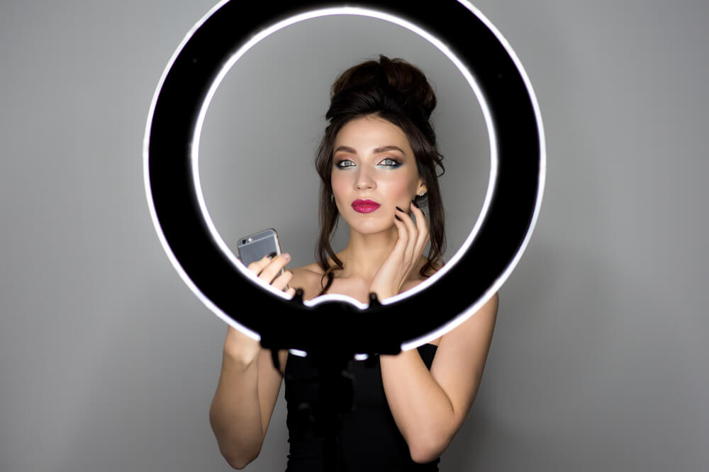 Glamorous model takes a selfie in front of a ring light. - selfie lights iPhone