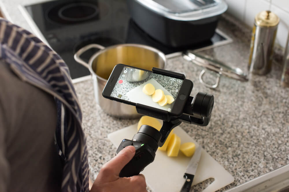 a person holding an iPhone on a gimbal, recording a video of sliced potatoes. - fixing blurry iPhone photos