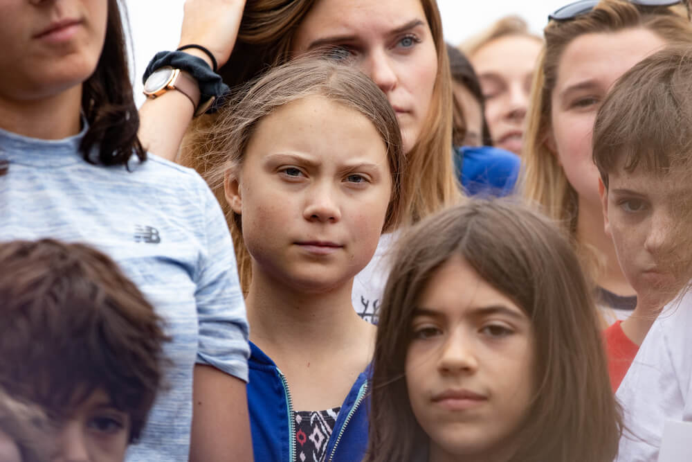 Greta Thunberg frowning in a crowd of children. - make money iPhone photos