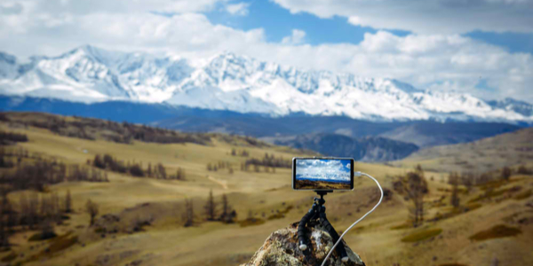 Smartphone on small tripod takes pictures of the mountain range and the clouds above the snowy peaks. Blurred background, focus on display. Photo travel around the world.