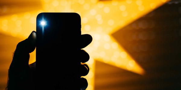 Man holding the new phone with yellow star bokeh background featuring a flare flash light from the rear flash and camera - holiday concept