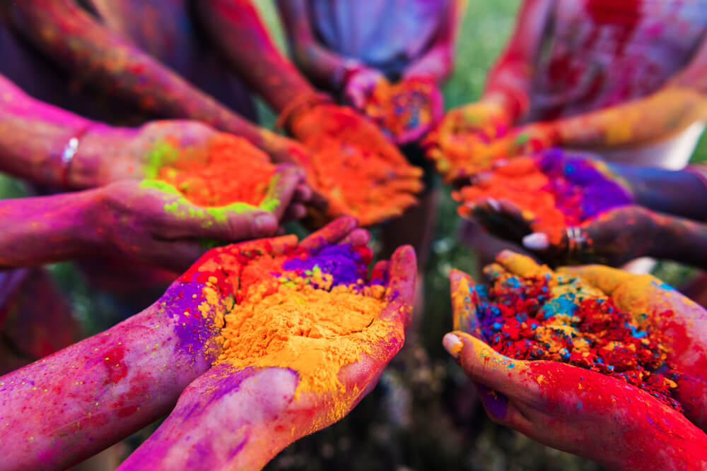 colorful festival, a group of people showing their hands with colored powder - image format for iPhone