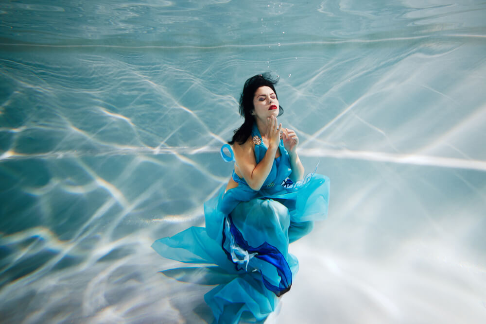 elegant model in light blue dress underwater