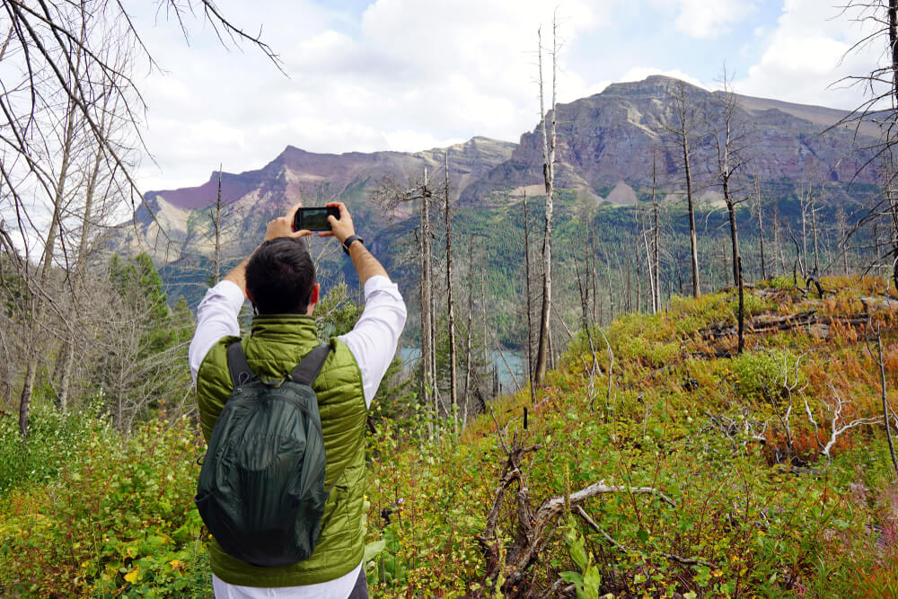 man taking a scenic photo of nature on phone - iPhone photography courses
