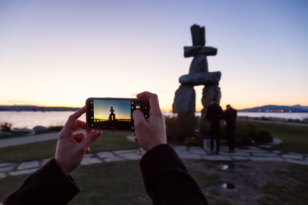 two hands taking a photo of a statue on a phone