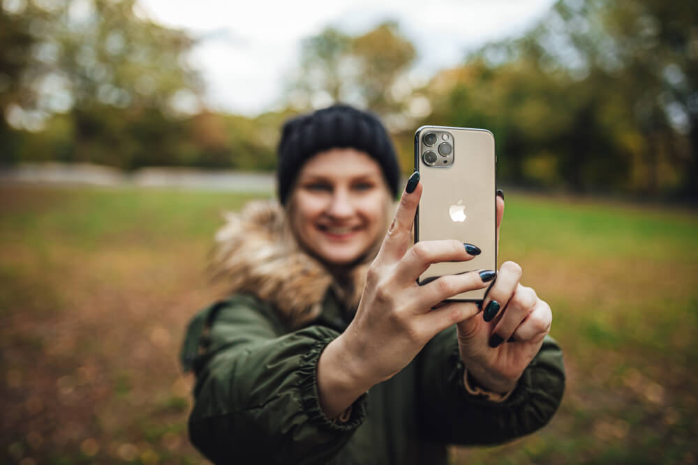 girl takes a selfie on iPhone 11, wearing a fur coat in Fall season - 30% selfie distortion