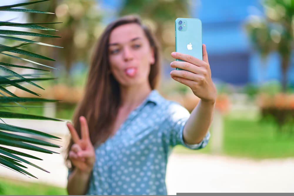 girl takes a selfie with a peace sign on her iPhone 11 - 30% selfie distortion