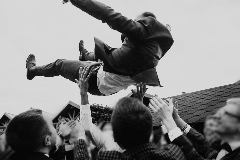 groom being thrown in the air