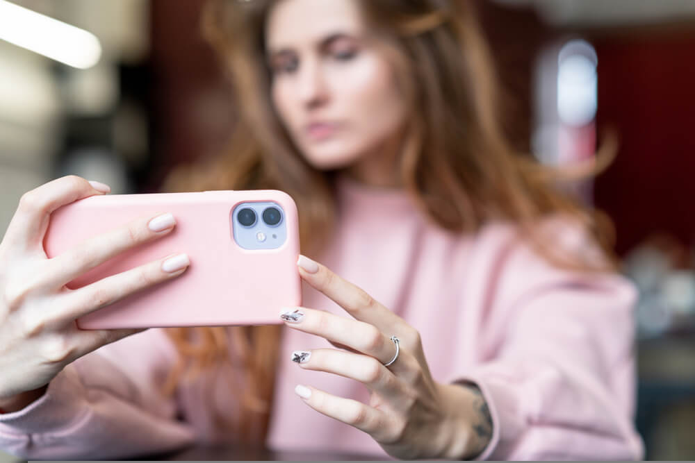 woman in pink sweater takes a selfie on iPhone 11