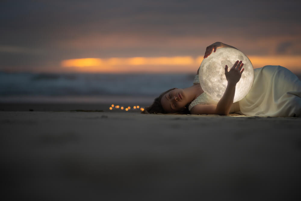 woman lying and hugging the moon at twilight