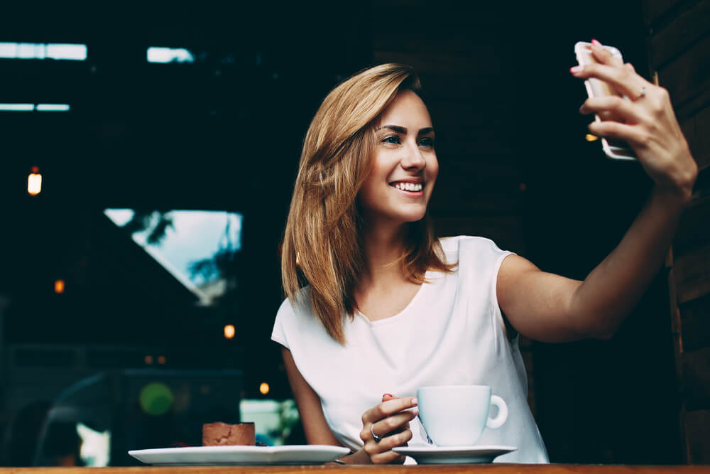 caucasian girl taking a selfie on her iPhone - iPhone camera gestures
