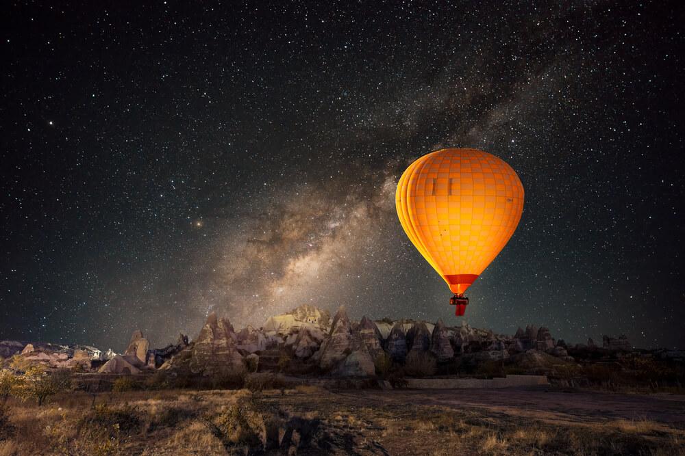night photo of hot air balloon and night sky full of stars