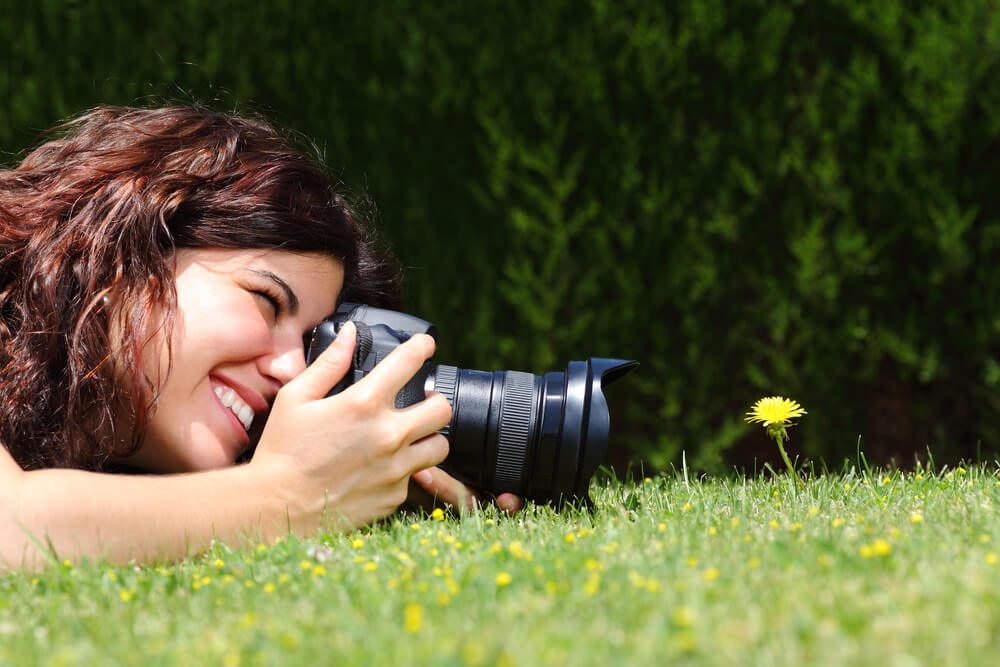 smiling woman using camera to capture small flower - macro photography cameras