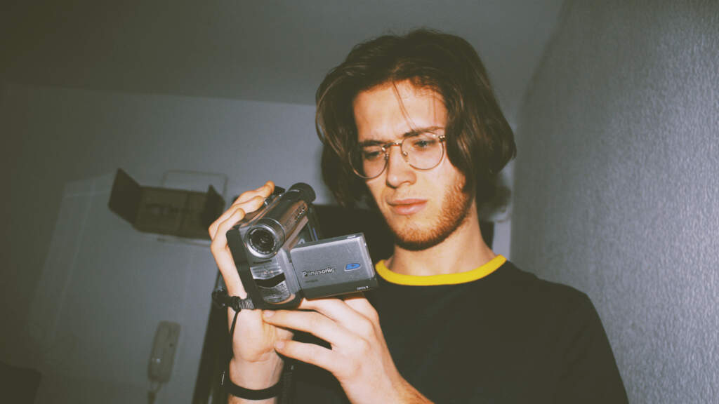 best cheap video camera - a guy with long hair holding and looking at a camcorder