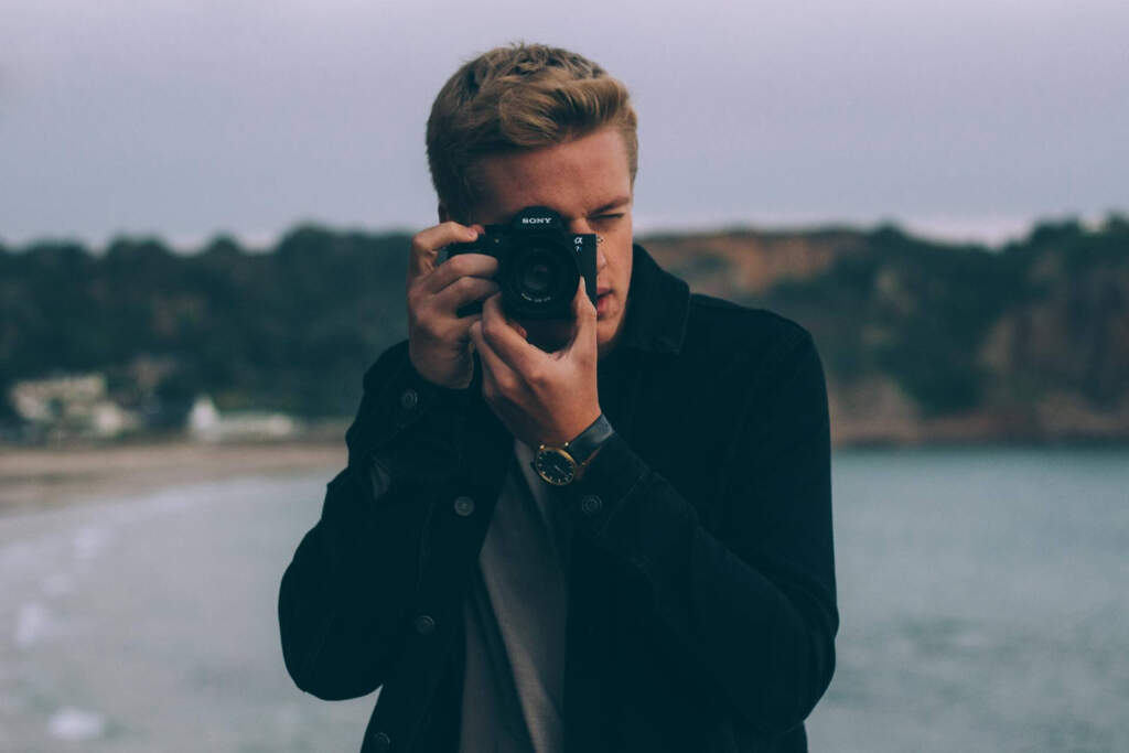 caucasian guy taking a photo using a DSLR camera - best low light video cameras