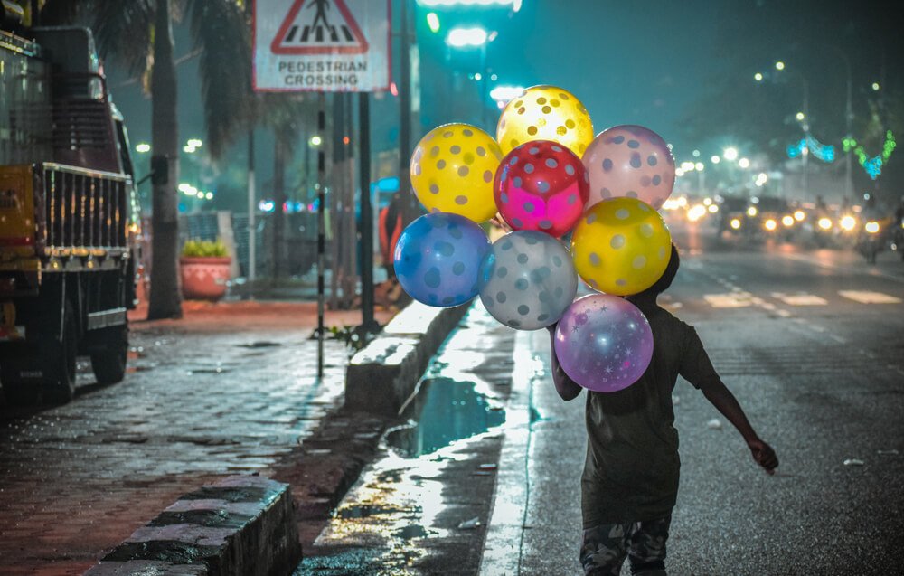 kid carrying colorful balloons in the night