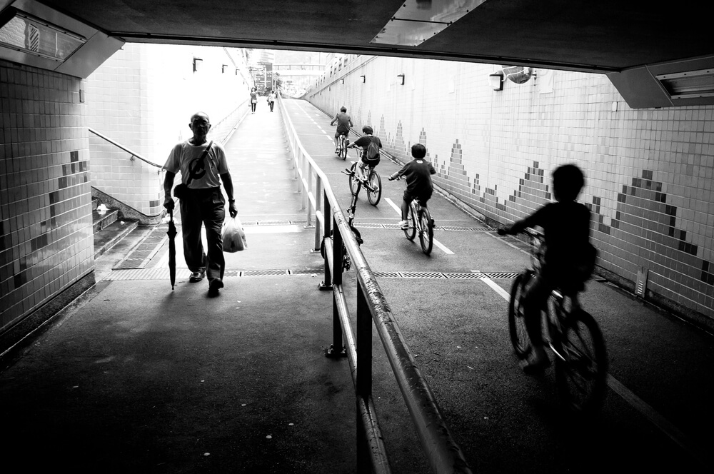 street photo of old man walking and children riding bikes - iPhone camera techniques