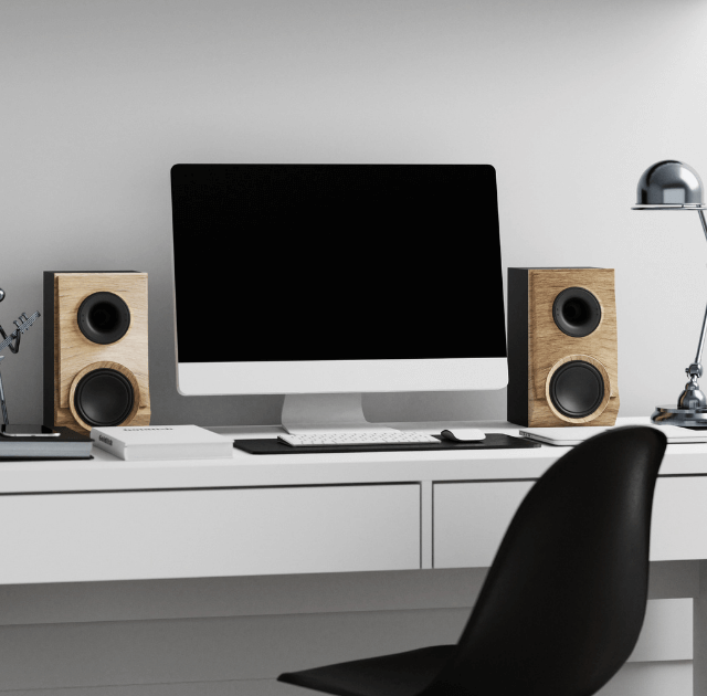 best bookshelf speakers under 1000 - a white office desk with black chair, computer, and bookshelf speakers